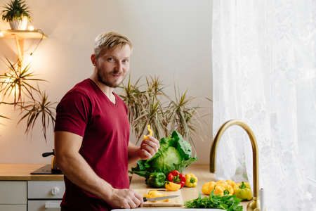 A blonde man tastes bell peppers in the kitchen. A man is cutting vegetables by the window in a beautiful interior. Harvesting and preparing food.