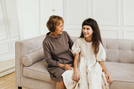 Family concept. Grandmother and granddaughter are sitting on the sofa in a light interior.