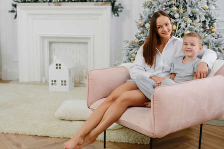 Beautiful portrait of a woman and her son in a New Years interior. Happy loving family. The child hugs his mom against the background of the Christmas tree .. Concept of Christmas and New Year.