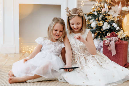 two blonde girls are looking at a mobile phone. Sisters in the New Years interior. Christmas concept. Archivio Fotografico