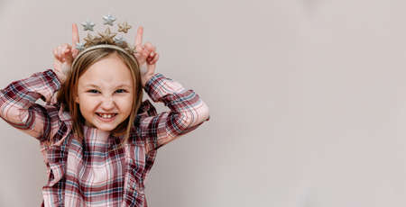 Funny portrait of a 10-year-old girl. the child shows horns. Emotional face.