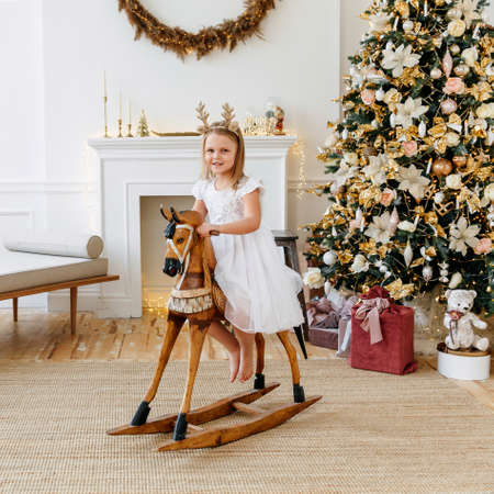 six-year-old blonde girl on a wooden horse. Beautiful Christmas home interior. New year concept. High quality photo