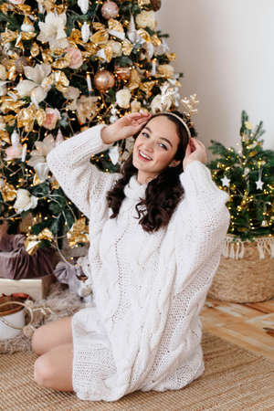 beautiful young woman in a white sweater sits on the floor against the background of a decorated Christmas tree. Christmas tree at home. Have a good mood on New Years Eve. Concept preparation for New Year holidays. High quality photo