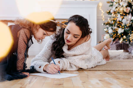 mom and little daughter in the New Year's interior write wishes on a piece of paper. Christmas tree at home. Have a good mood on New Years Eve. Concept preparation for New Year holidays. High quality photo