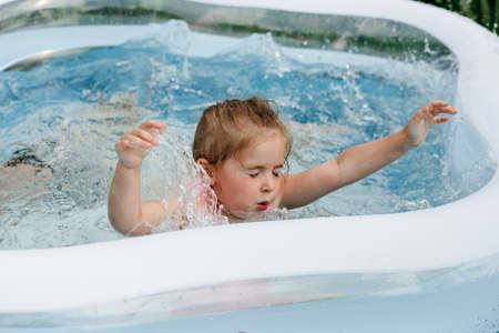 Little girl drowns in the home pool. Danger in the water. Baby bathes Foto de archivo