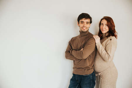 portrait of a happy couple, husband and pregnant wife on a light background. A man and a woman are near. Stock Photo