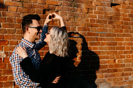 happy loving couple on a brick wall background. A man and a woman of European appearance make a heart shape with their hands. 스톡 콘텐츠