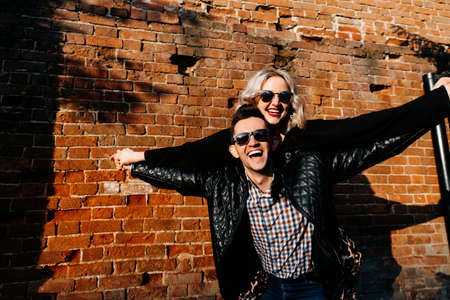 happy loving couple on a brick wall background. portrait of a man and a woman of European appearance laughing, holding hands, arms to the sides, depicting flight.