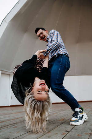 the man holds the falling woman in his arms. funny pose of a couple of people. a fun pastime for lovers