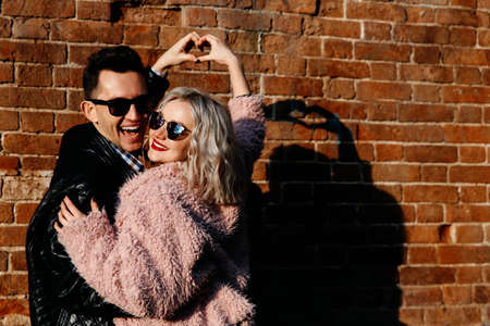 happy loving couple on a brick wall background. A man and a woman of European appearance make a heart shape with their hands. Stock Photo