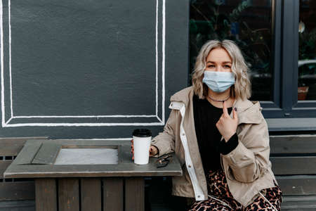 blonde woman sits at a table in a cafe on the street. A lady in a medical mask holds a glass of coffee