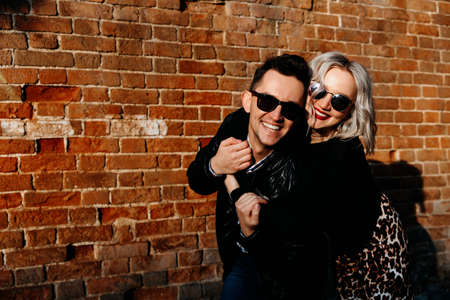 A couple of happy people hugging on a brick wall background. European man and woman in sunglasses laugh. Stock Photo