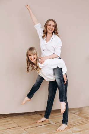 two happy women on a pink background. a woman rolls another on her back. giving a piggyback ride. Sit on your back. Female friendship concept.