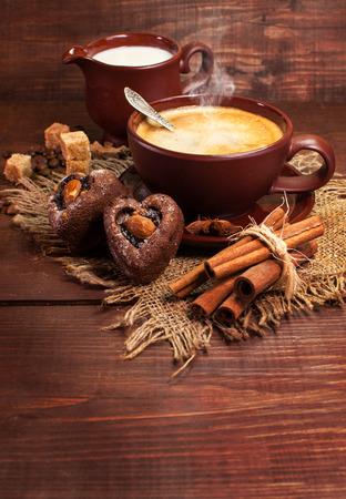 Del caffè vita ancora. Una tazza di caffè, dolci e spezie su una superficie in legno