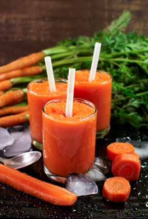 Glasses with carrot smoothies. Fresh carrot on a wooden surface.