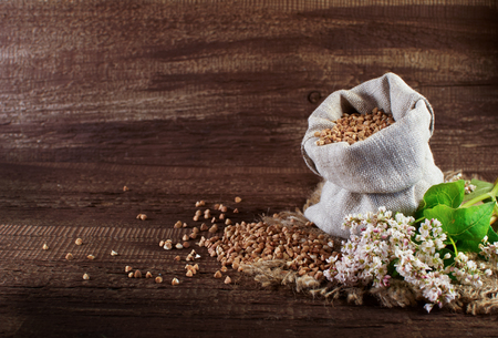 Buckwheat and buckwheat flowers on a wooden surface Stock Photo