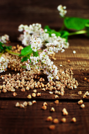 Flowers and buckwheat groats on a wooden surface. Zdjęcie Seryjne