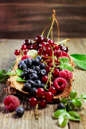 Variety of summer berries in tub on a wooden surface.