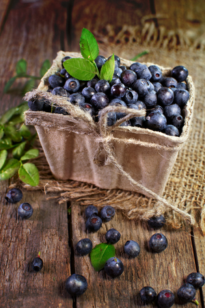 Close-up of blueberries in a basket on a wooden surface.