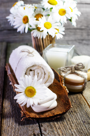 Spa still life. Beautiful daisies, candle, aromatic oils and other spa accessories on wooden surface. Zdjęcie Seryjne
