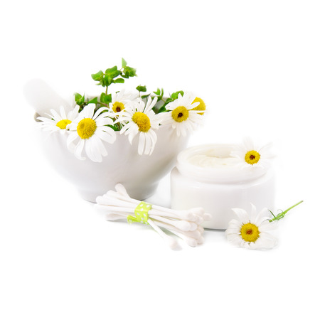 Natural cosmetics concept. Beautiful daisies, jar of cosmetic cream and hygienic sticks on a white background.