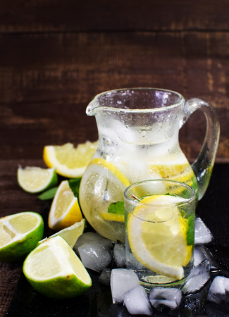 Pitcher with fresh fruit tonic water. With lemon, mint and lime. On a wooden surface. Zdjęcie Seryjne