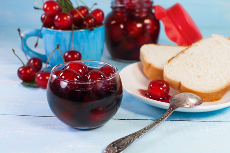 Breakfast still-life. A delicious cherry jam and toast bread. On a blue wooden surface.