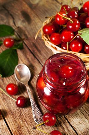 mermelada: deliciosa mermelada de cereza en un fondo de madera.