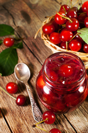 delicious cherry jam on a wooden background.