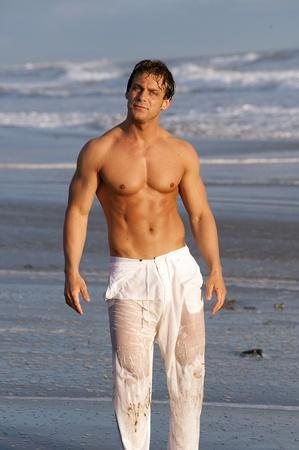 pantalones vaqueros mojados: hombre en la playa Foto de archivo
