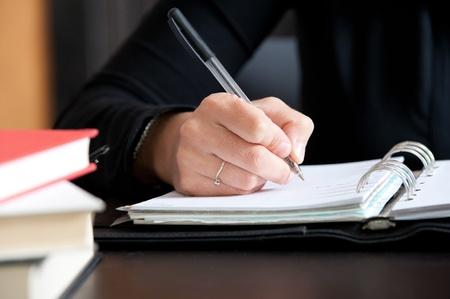 Close up woman hand writing notes on calendar Standard-Bild