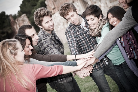 A group of multiracial students with hands on stack photo