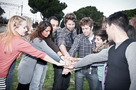 A group of multiracial students with hands on stack