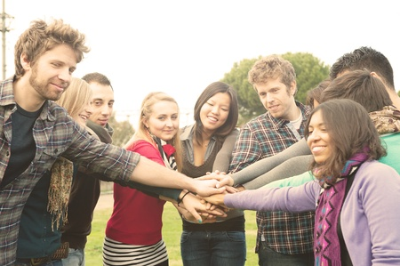 a group of multiracial students whit hands on stack photo