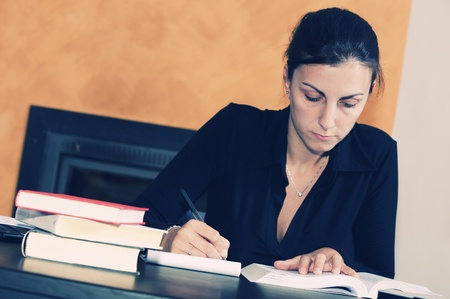 Stressed young woman sitting at a table among books and papers on  photo