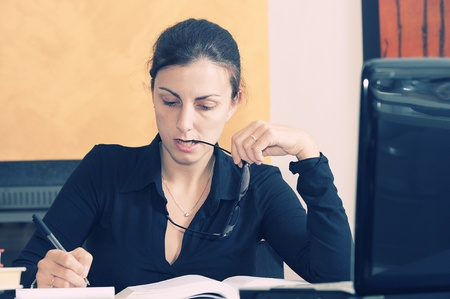 young female university student studying at table photo