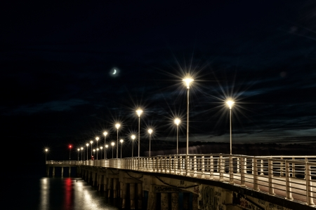 lamp posts on a pier at night