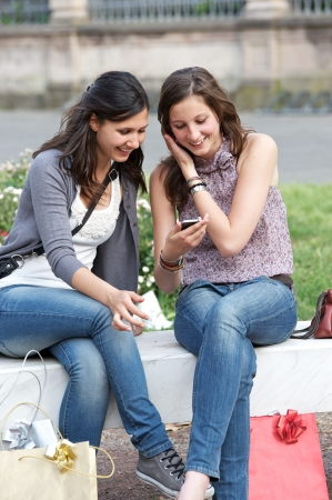 Two shopping girls in park with a mobile phone, italy