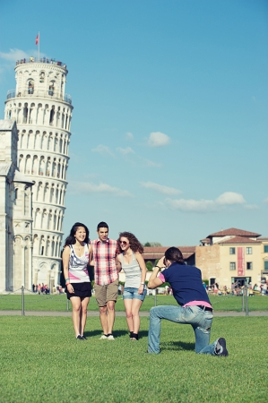 Group of Friends Taking Photo with Pisa Leaning Tower on Background , Italy photo
