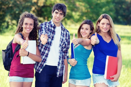 Young group of happy students showing thumbs up sign together outdoor in the park Italy Stock Photo