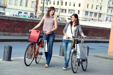 Two Beautiful Women Walking in the City with Bicycles and Bags,Italy