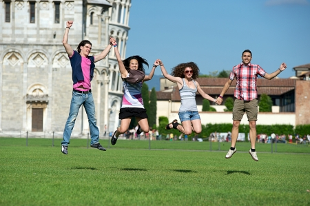 piazza dei miracoli: Group of Friends Jumping with Pisa Leaning Tower on Background Italy Stock Photo