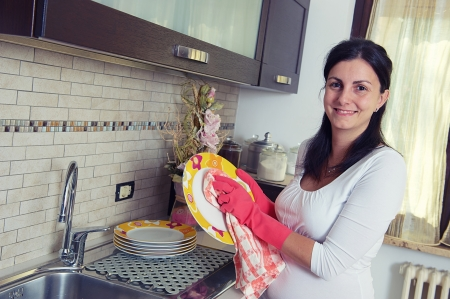 Beautiful brunette woman washing the dishes in the kitchen, Italy