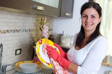 ama de casa: Hermosa mujer morena lavar los platos en la cocina, Italia