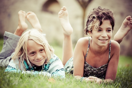 Two kids lying on top of grass,Italy photo
