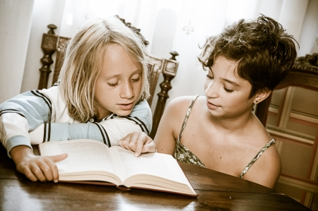 storytime: Portraits of young childs reading a book ,Italy