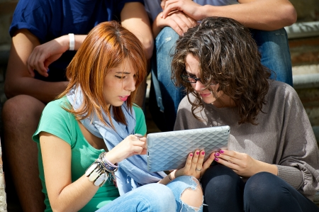 freetime: Laughing teenagers looking at the touchpad screen outdoors ,Italy Stock Photo