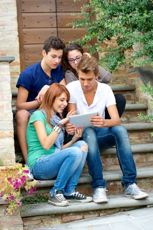 Laughing teenagers looking at the touchpad screen outdoors ,Italy Stock Photo