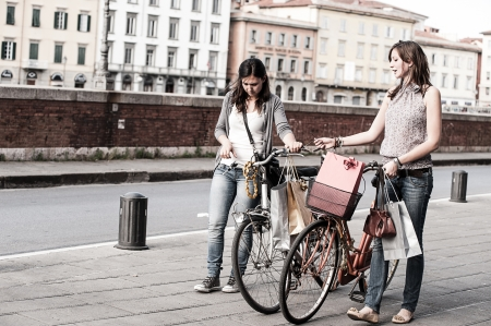 Two Beautiful Women Walking in the City with Bicycles and Bags,Italy photo