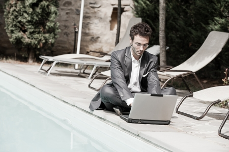 laptop outside: Young Businessman with Computer next to Swimming Pool Italy